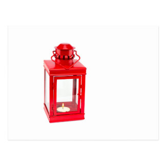 Red lantern with burning tealight on white postcard