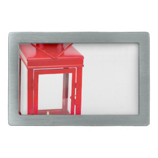 Red lantern with burning tealight on white rectangular belt buckle