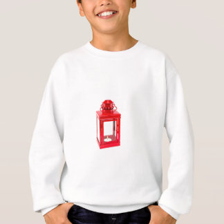Red lantern with burning tealight on white sweatshirt
