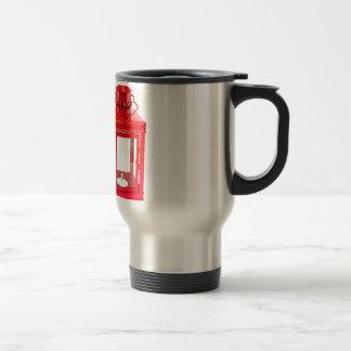 Red lantern with burning tealight on white travel mug