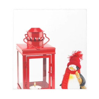 Red lantern with penguin figurine on white notepad