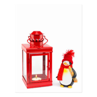 Red lantern with penguin figurine on white postcard