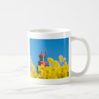 Red lighthouse in a yellow canola field coffee mug