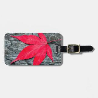 Red maple leave on black burnt wood luggage tag