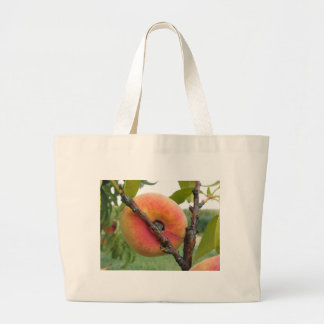 Red peaches hanging on the tree . Tuscany, Italy Large Tote Bag