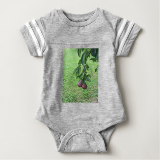 Red pears hanging on a growing pear tree baby bodysuit