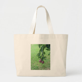 Red pears hanging on a growing pear tree large tote bag