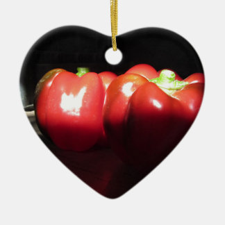 Red peppers illuminated by sunshine in the dark ceramic heart ornament