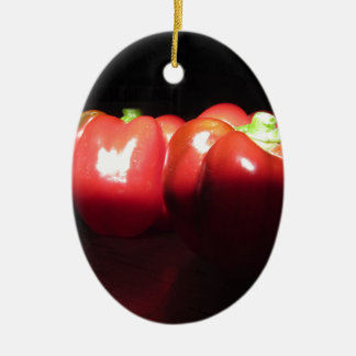 Red peppers illuminated by sunshine in the dark ceramic oval ornament