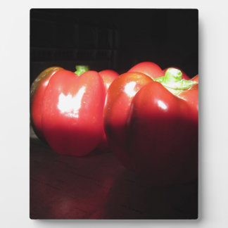 Red peppers illuminated by sunshine in the dark plaque