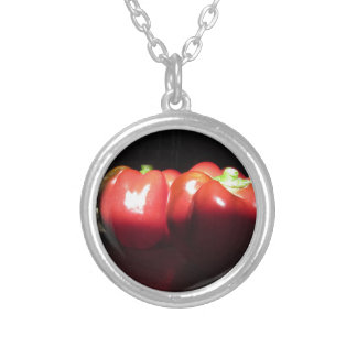 Red peppers illuminated by sunshine in the dark silver plated necklace