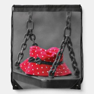 Red Polka Dot Hat Forgotten on a Swing Drawstring Bag