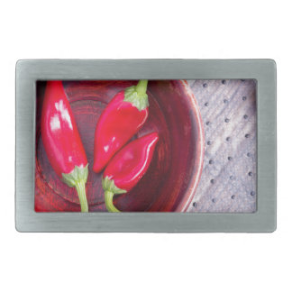 Red raw pepper in a brown wooden bowl belt buckles