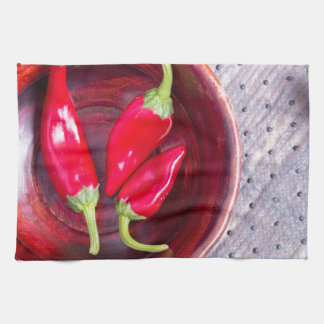 Red raw pepper in a brown wooden bowl hand towels