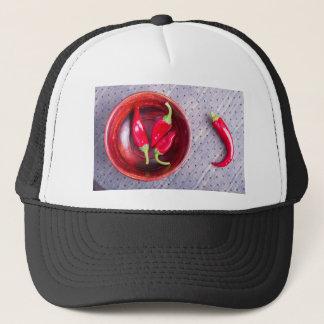 Red raw pepper in a brown wooden bowl trucker hat