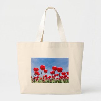 Red tulips field from below with blue sky large tote bag