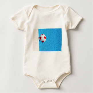 Red-white beach ball floating  in swimming pool baby bodysuit