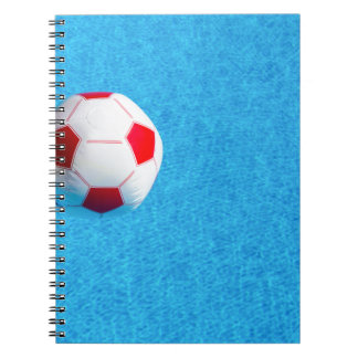 Red-white beach ball floating  in swimming pool notebooks