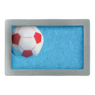 Red-white beach ball floating  in swimming pool rectangular belt buckles