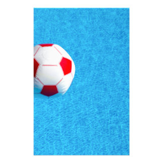 Red-white beach ball floating  in swimming pool stationery