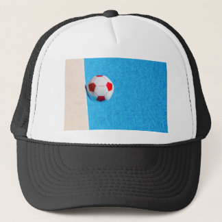 Red-white beach ball floating  in swimming pool trucker hat