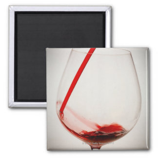 Red wine pouring into glass, close-up square magnet