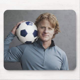 Redhead holding a soccer ball on his shoulder mouse pad