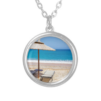 Reed beach umbrella with loungers on beach at sea. silver plated necklace