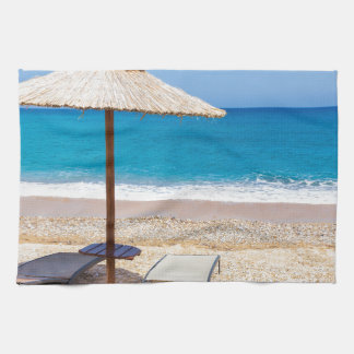 Reed beach umbrella with loungers on beach at sea. towels