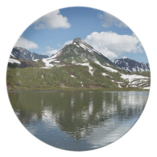 Reflection of sky and clouds in mountain lake party plates