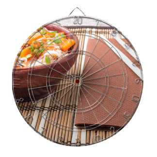 Rice vermicelli hu-teu in a small brown bowl dartboard with darts
