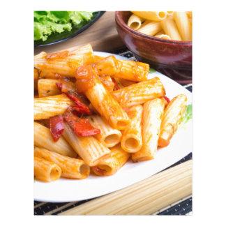 Rigatoni pasta, seasoned with pepper and arugula letterhead