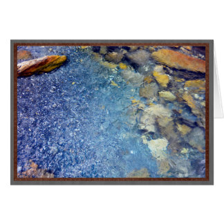 Rippling blue water and rocks. card