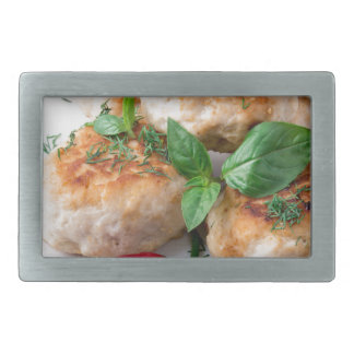 Rissole of minced chicken on a white plate belt buckles