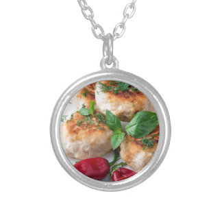 Rissole of minced chicken on a white plate silver plated necklace