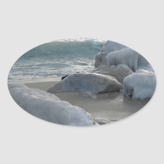 Rocks covered in ice on the sea shore oval sticker
