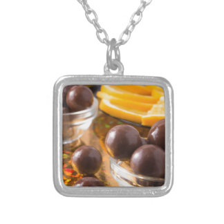 Round candy  from chocolate close-up on a colorful silver plated necklace