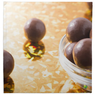 Round chocolate candy in small glass cup on color napkin