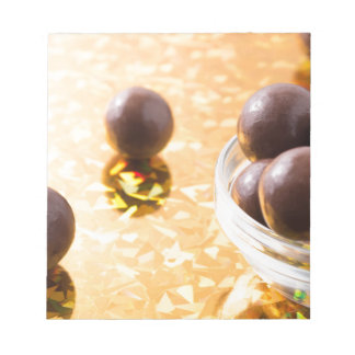 Round chocolate candy in small glass cup on color notepad