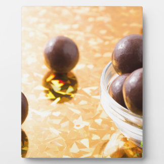 Round chocolate candy in small glass cup on color plaque