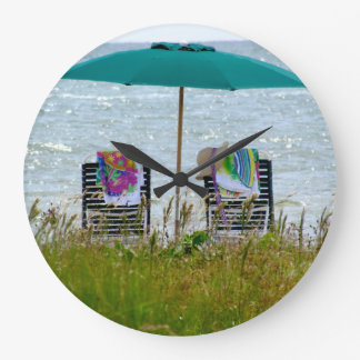 Round clock with no numbers.  Beach scene.