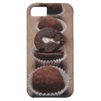Row of chocolate truffles on wood iPhone 5 cover