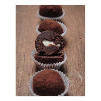 Row of chocolate truffles on wood postcard