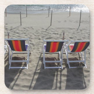 Row of colorful wooden chairs at beach beverage coaster