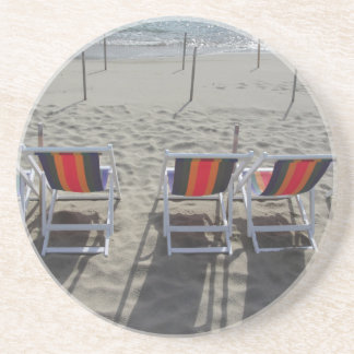 Row of colorful wooden chairs at beach drink coaster