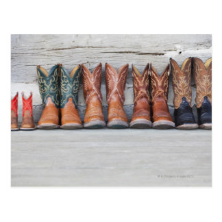 Row of cowboy boot on porch of log cabin postcard