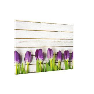row of purple tulips on wood canvas print