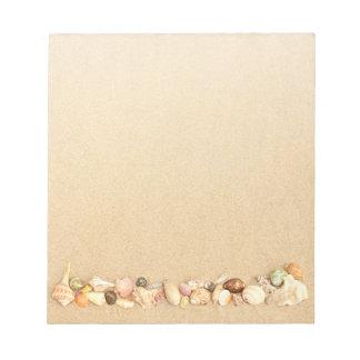 Row of Seashells on Beach Sand Notepads