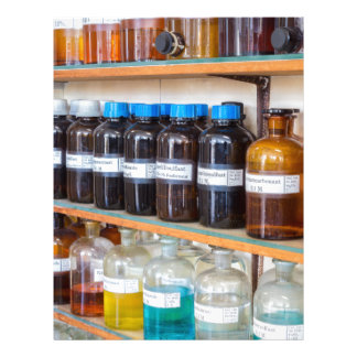 Rows of fluid chemicals in bottles at chemistry letterhead
