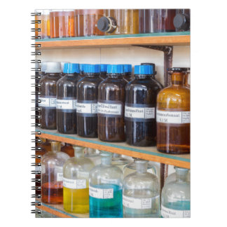 Rows of fluid chemicals in bottles at chemistry notebooks